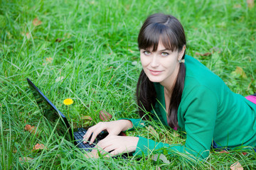 beautiful girl lying in the grass with laptop