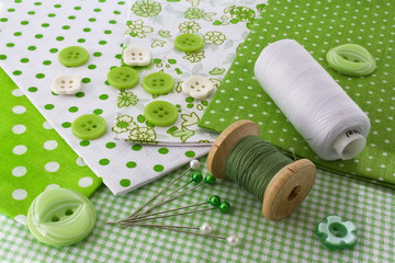 Accessories for sewing: threads, fabric, buttons in green-white