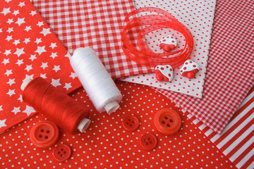 Accessories for sewing: threads, fabric, buttons in red-white co