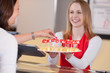 freundliche verkäuferin bietet käse zum probieren an - 31429901