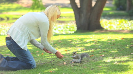Young woman feeding a squirrel