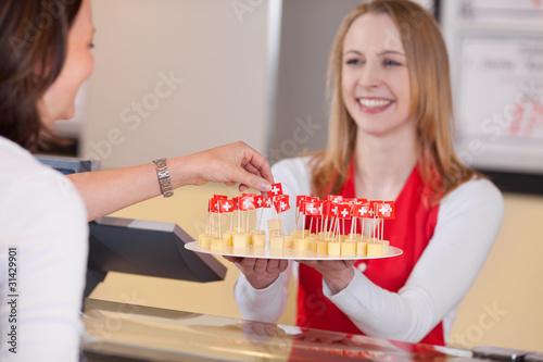Leinwanddruck Bild freundliche verkäuferin bietet käse zum probieren an
