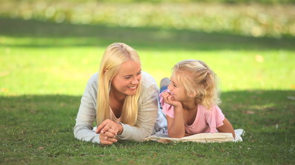 Young woman lying on the grass with her daughter