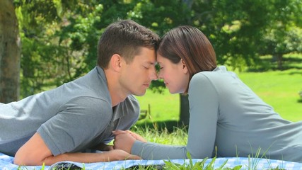 Loving young couple relaxing on the grass