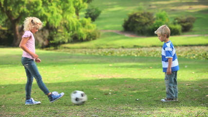 Two young children playing together with a ball