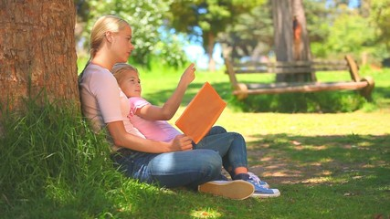 Young woman and her daughter reading