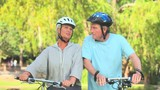 Mature couple talking while walking with their bikes