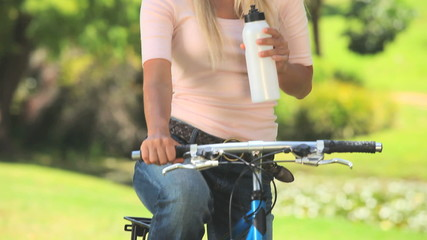 Young woman taking a drink of water while cycling