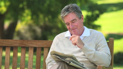 Mature man reading a newspaper on a bench