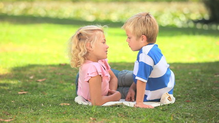 Two young children talking together