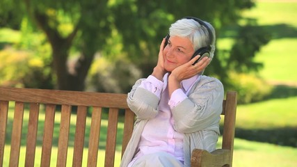 Elderly woman listening to music on a bench