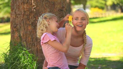 Young girl giving a flower to her mother