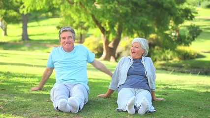 Mature couple doing their stretches outside
