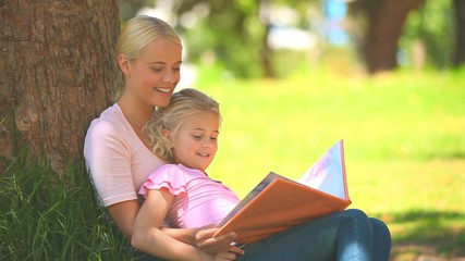 Young girl reading a book with her mother