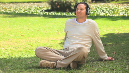 Young man listening to music on the grass
