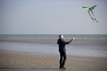 A senior man flying a kite on the beach