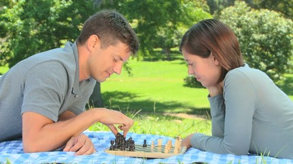 Young couple playing chess on the grass