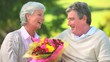 Elderly couple holding a bunch of flowers while sitting on a bench