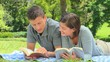 Young couple reading a book while lying on the grass