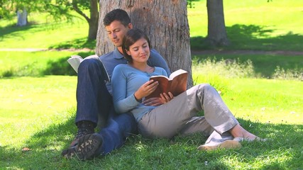 Young couple reading  book outdoors