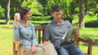 Young couple reading a newspaper