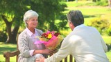 Mature man offering a bunch of flowers to his wife