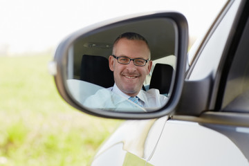businessman in car smiling at camera