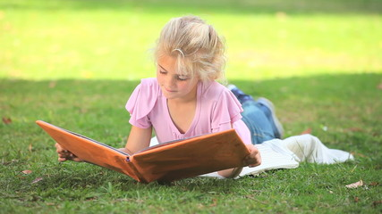 Young girl reading a book outdoors