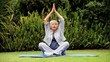 Grey-haired woman practising oriental exercises in garden