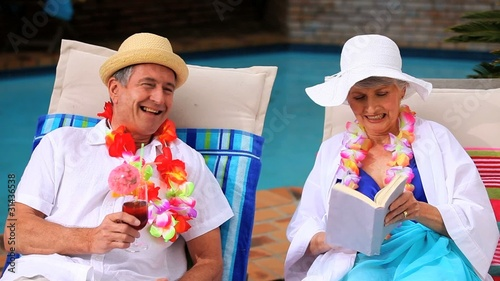 Mature couple with garlands chatting in deckchairs