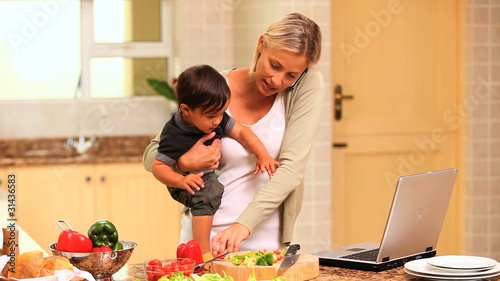 Busy woman phoning and dealing with her baby and her laptop