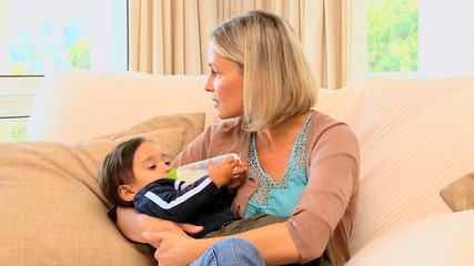 Young mother bottle-feeding baby on sofa