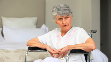 Elderly grey-haired woman thinking in a wheelchair