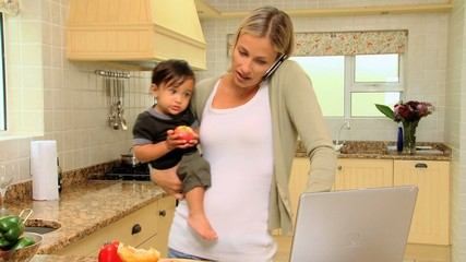 Young mother in kitchen coping with laptop phone and baby