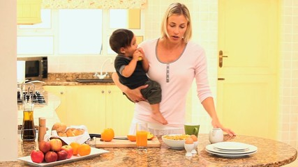 Mother busy in kitchen holding baby while father late for work
