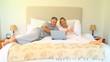 Couple on bed enjoying something hilarious on laptop