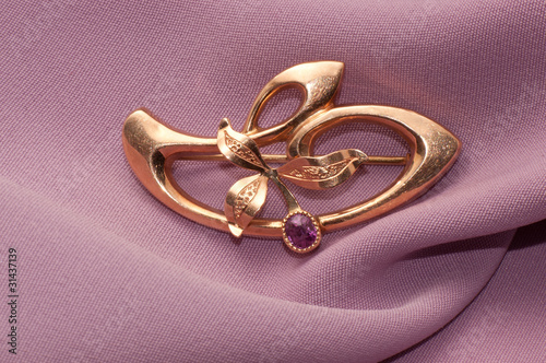 Golden brooch with amethyst