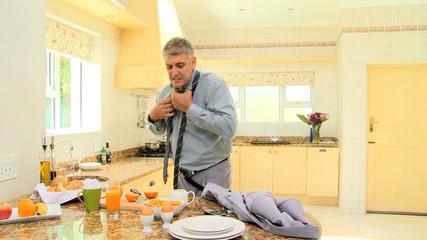 Man in kitchen hurriedly putting on tie