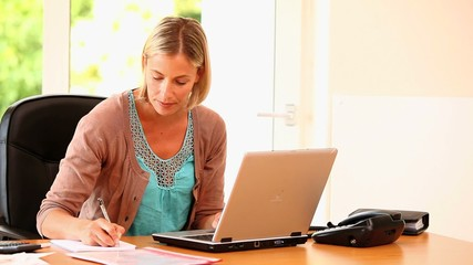 Young woman working on a laptop and answering a call