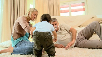 Young woman on carpet blowing bubbles for baby and husband