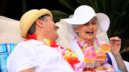Senior couple laughing and sharing cocktails