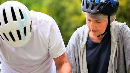 Mature couple getting ready for riding bicycles
