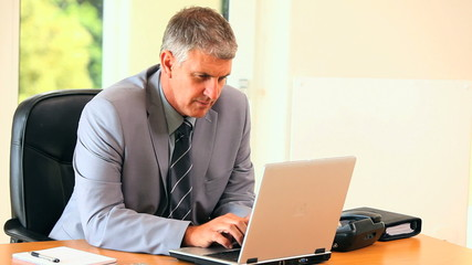 Middle-aged man in suit working on a laptop