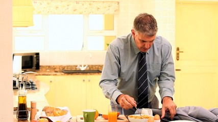 Man in kitchen receiving a call while rushing with breakfast