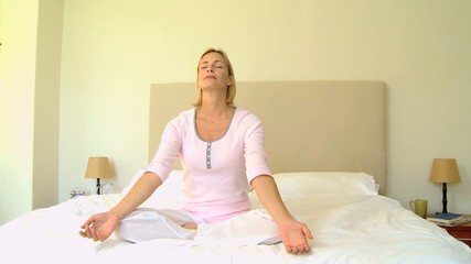 Young woman relaxing with yoga on bed