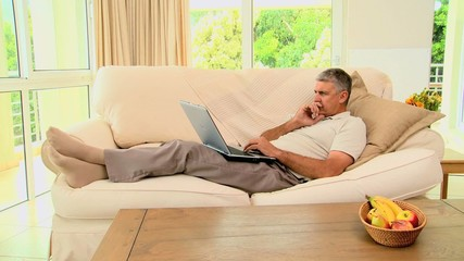 Man lying on sofa excited about something on laptop