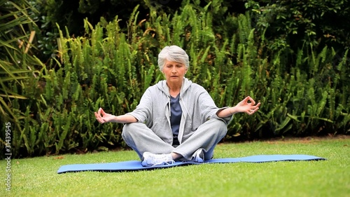 Grey-haired woman doing yoga in the garden