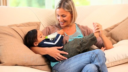 Young mother bottle-feeding her toddler on a sofa