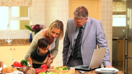 Doting parents trying to entertain baby in kitchen
