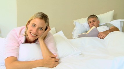 Blonde  woman posing on a bed while husband reads a book